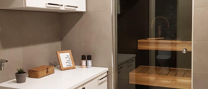Kodinhoitohuoneessa moderni laatoitus ja tyylikäs lasiovi saunaan