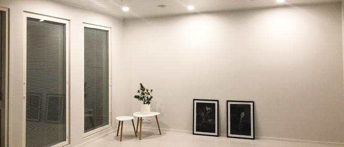 Avara ja tilava olohuone, jossa lattiatasosta lähtevät korkeat ikkunat