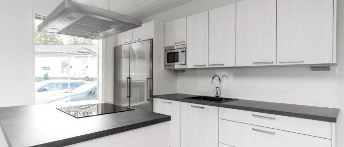 moderni valkoinen keittiö, jossa liesi saarekeratkaisussa
