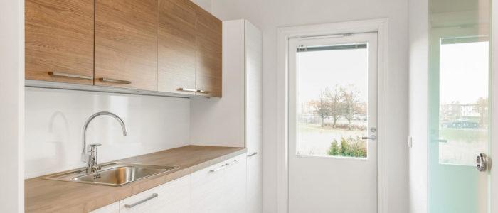 Kodinhoitohuoneessa harmaa lattialaatoitus, moderni Puustellin kalustus ja maitolasinen lasiovi suihkuhuoneeseen
