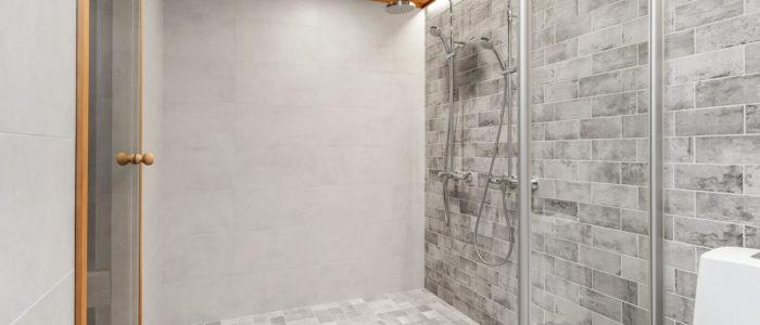 Kylpyhuoneessa vaaleanharmaa laatoitus ja kaksi suihkua, wc-istuin ja käynti saunaan